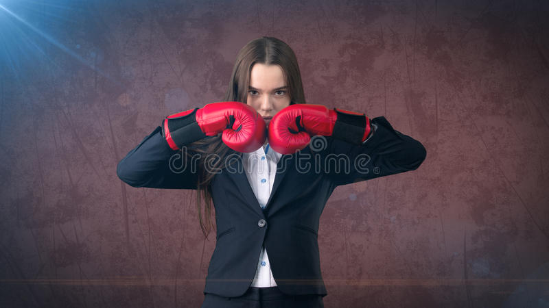 Young beautiful woman in black suit and white shirt standing in combat pose with red boxing gloves. Business concept. Young business woman dress in black suit stock photography