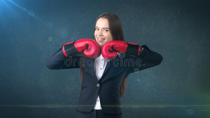 Young beautiful woman in black suit and white shirt standing in combat pose with red boxing gloves. Business concept. Young business woman dress in black suit royalty free stock photography