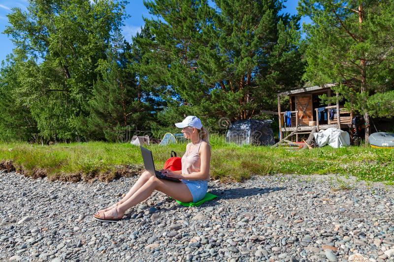 A young beautiful woman blonde in a white cap and denim shorts sits on the rocky shore of the river with a laptop on her knees and royalty free stock photography