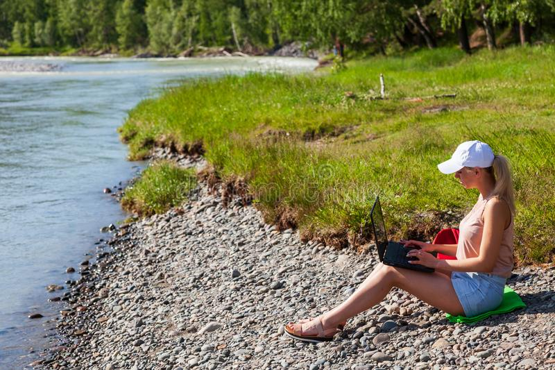 A young beautiful woman blonde in a white cap and denim shorts sits on the rocky shore of the river with a laptop on her knees and stock image