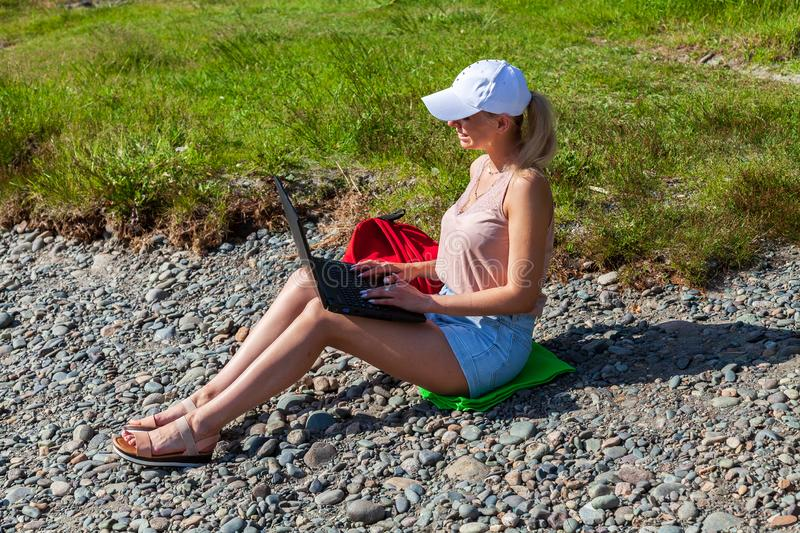 A young beautiful woman blonde in a white cap and denim shorts sits on the rocky shore of the river with a laptop on her knees and stock photography