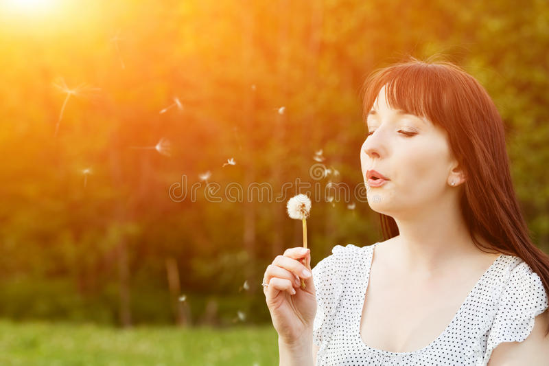 Young beautiful woman blowing a dandelion in spring. Scenery. Happiness, harmony, wellness, relaxation concepts royalty free stock image