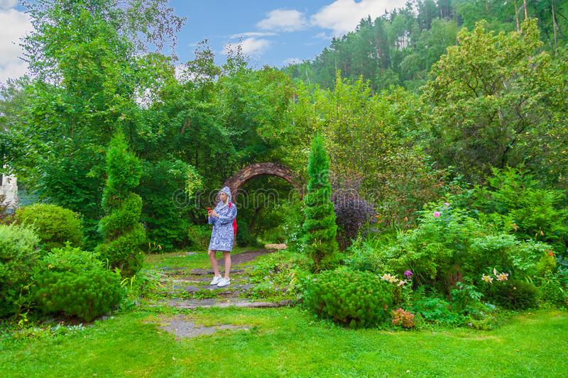 A young beautiful woman in a blue raincoat with a phone in garden park  on summer day with green bushes under blue sky. Tourism royalty free stock photography