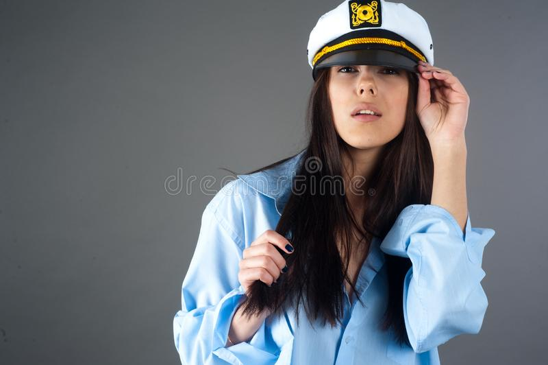 Portrait of young pretty woman in captain hat stock images