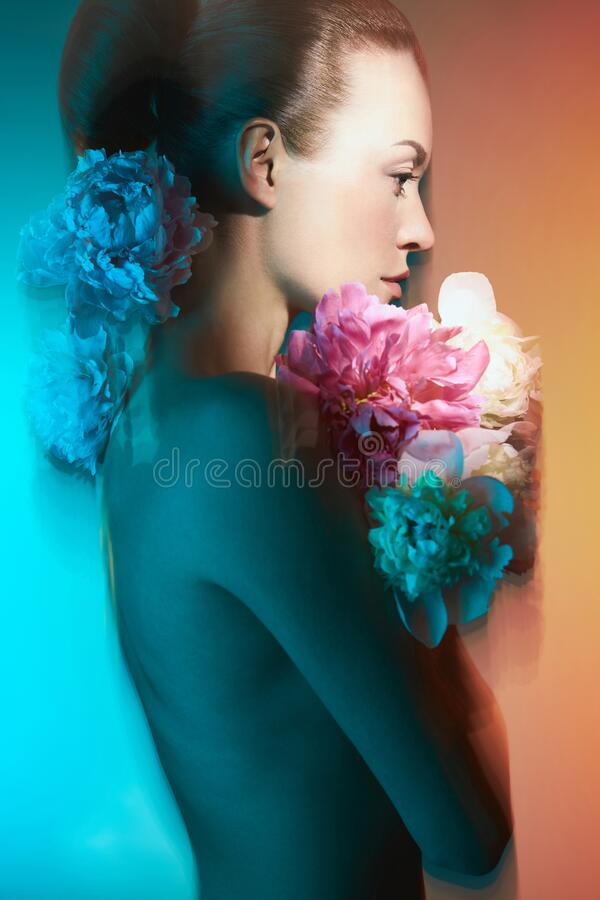 Young beautiful woman with bouquet of roses. Professional art makeup royalty free stock photo