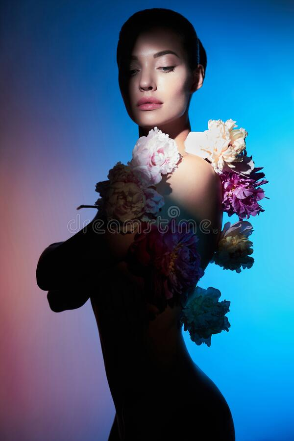 Young beautiful woman with bouquet of roses. Professional art makeup stock image