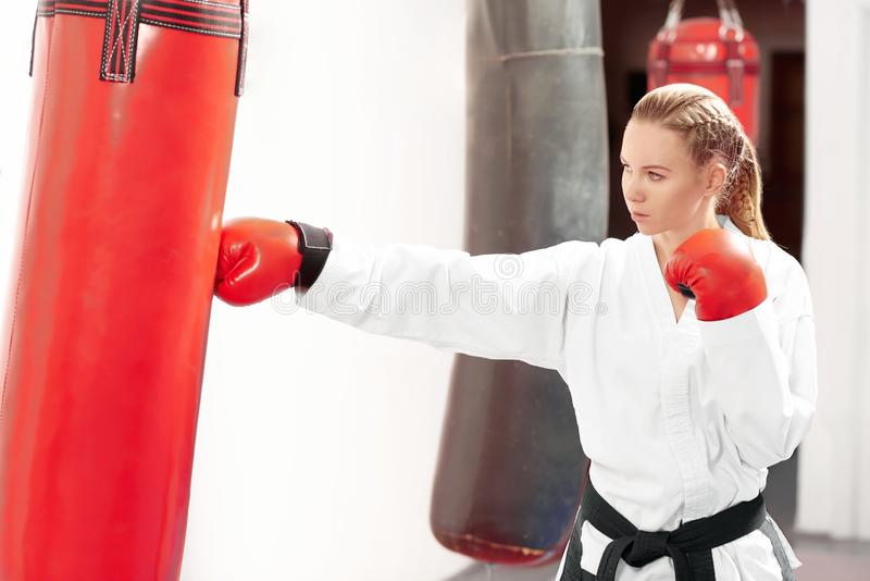 Young beautiful woman boxing heavy red bag with strong kick in gym. stock image