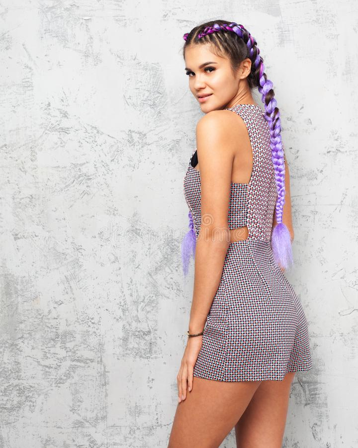 Young beautiful woman with braids posing in profile on a gray background in a fashionable summer outfit. Indoor. royalty free stock photo
