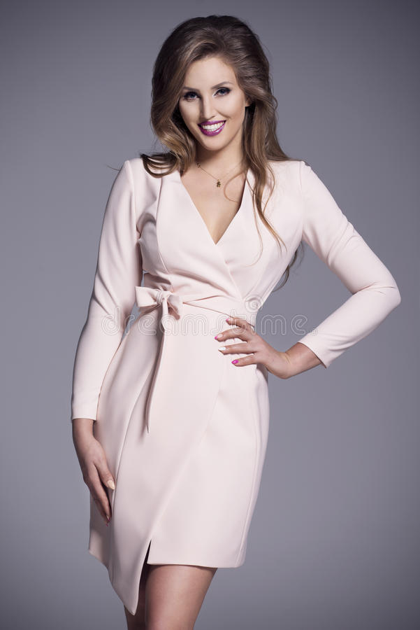 Young beautiful woman in a bright pink business dress stock image