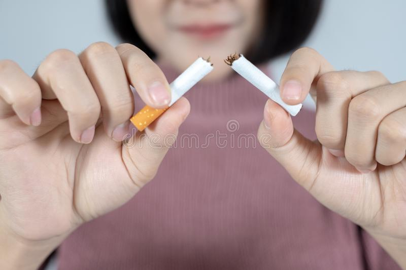 Young beautiful woman with broken cigarette. Stop smoking concept. The word stop smoking on a black background,stop smoking royalty free stock photo