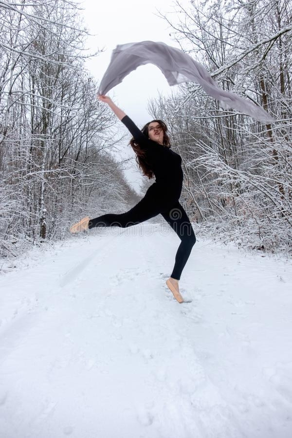 Young beautiful woman brown-haired girl in black ballet suit dances peak in snowy winter forest stock image