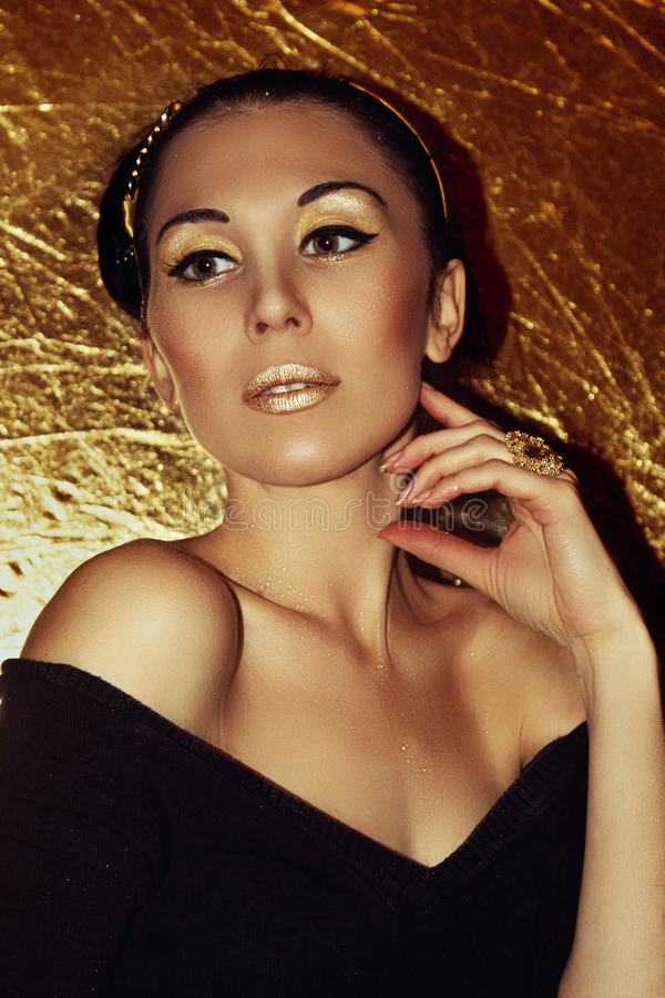 Young beautiful woman brunette with retro hairstyle, hoop. Gold make-up. stock image