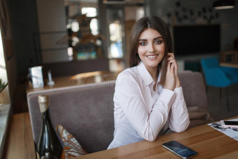 Young beautiful woman, brunette, sitting alone at a table in a cafe. Beautiful woman at a table in a cafe.Young beautiful woman, brunette, sitting alone at a royalty free stock photography