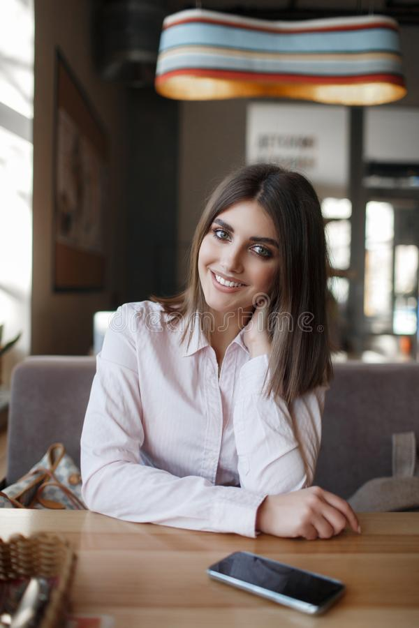 Young beautiful woman, brunette, sitting alone at a table in a cafe. Beautiful woman at a table in a cafe.Young beautiful woman, brunette, sitting alone at a stock images
