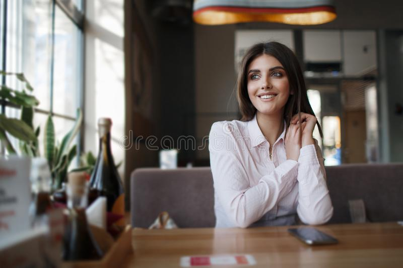 Young beautiful woman, brunette, sitting alone at a table in a cafe. Beautiful woman at a table in a cafe.Young beautiful woman, brunette, sitting alone at a royalty free stock photos