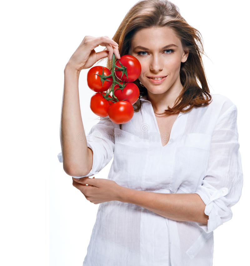Young beautiful woman with bunch of tomatoes in hand isolated on white background. Intriguing girl of european appearance in a white shirt holding a bunch of stock images