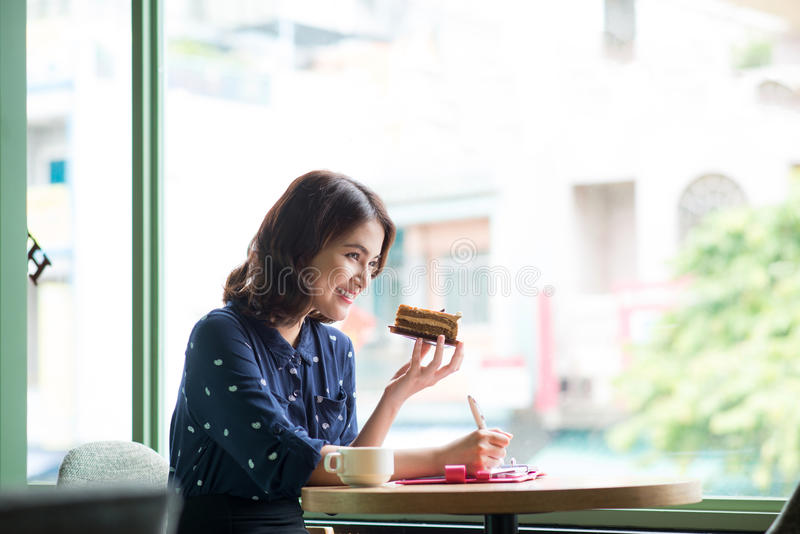 Young beautiful woman in the cafe near the window, thinking and. Writing something with cake in hand stock photo