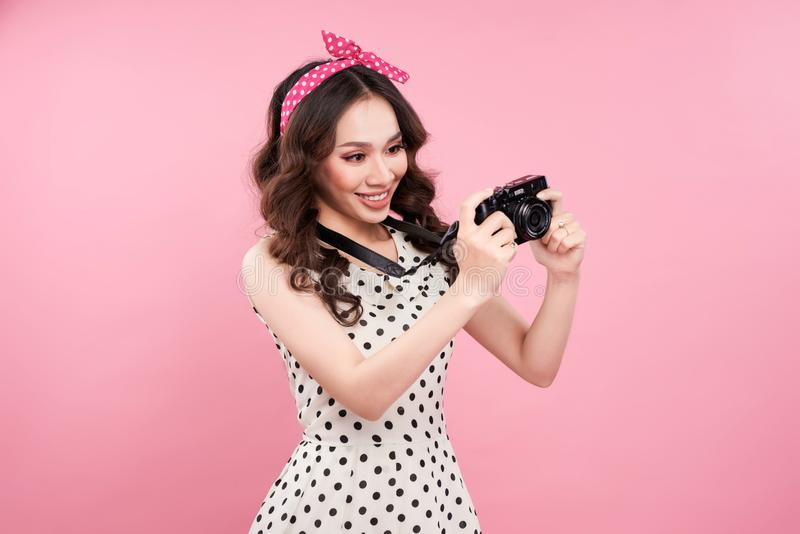 Young beautiful woman with camera on pink background royalty free stock photos