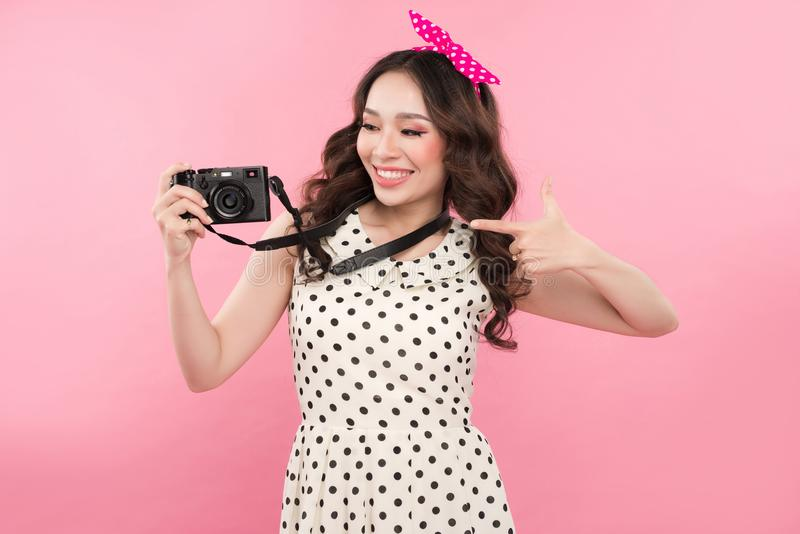 Young beautiful woman with camera on pink background royalty free stock photography