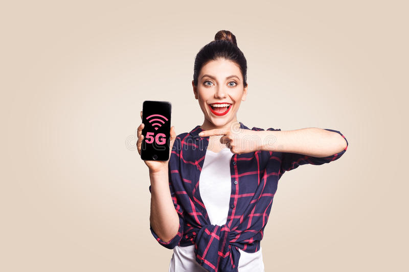 Young beautiful woman in casual style holding phone looking at camera and showing 5G internet on phone display with finger. Studio shot on beige background stock images