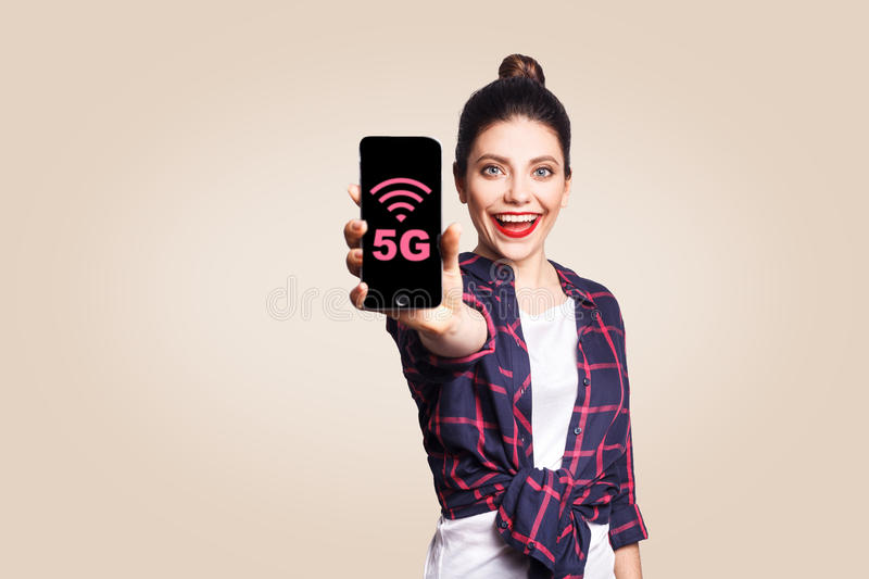 Young beautiful woman in casual style holding phone looking at camera and showing 5G internet on phone display. Studio shot on beige background stock photos