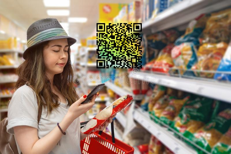 Young beautiful woman chooses products in the supermarket and checks the QR code on the label. The concept of modern technology royalty free stock image