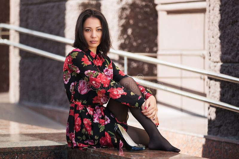 Young fashion woman in floral dress on city street royalty free stock images