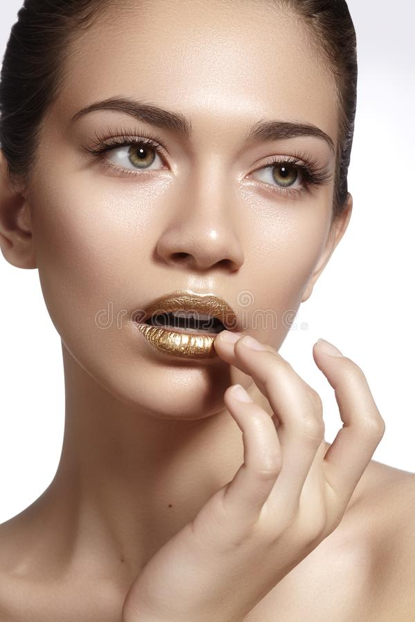 Young Beautiful Woman with clean soft Skin, bright gold Lips Makeup. Perfect eyebrows shapes. Day make-up stock image