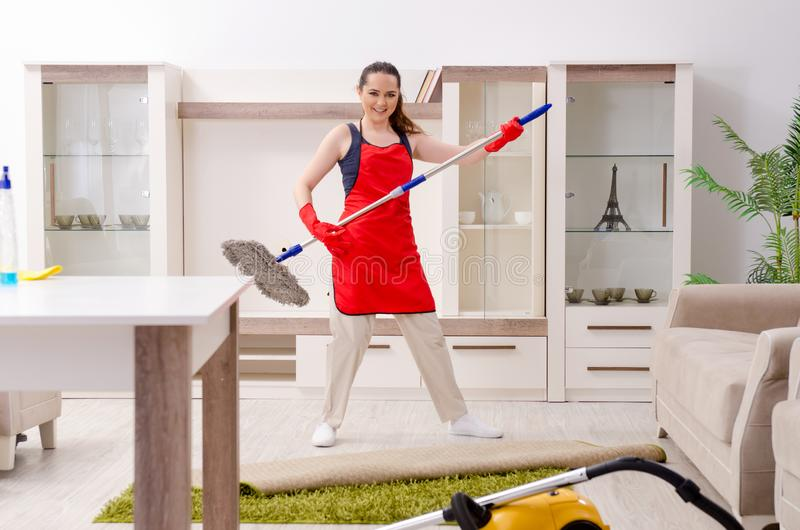 The young beautiful woman cleaning apartment royalty free stock images