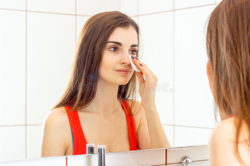Young beautiful woman cleans with facial makeup royalty free stock photos