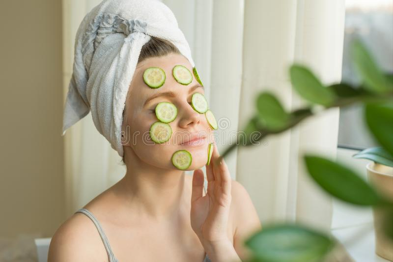 Young beautiful woman close-up at home near the window with natural homemade mask of cucumber on face, towel on head. Skin care, royalty free stock images