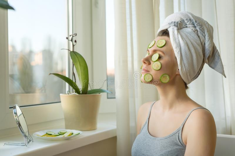 Young beautiful woman close-up at home near the window with natural homemade mask of cucumber on face, towel on head. Skin care, stock photo