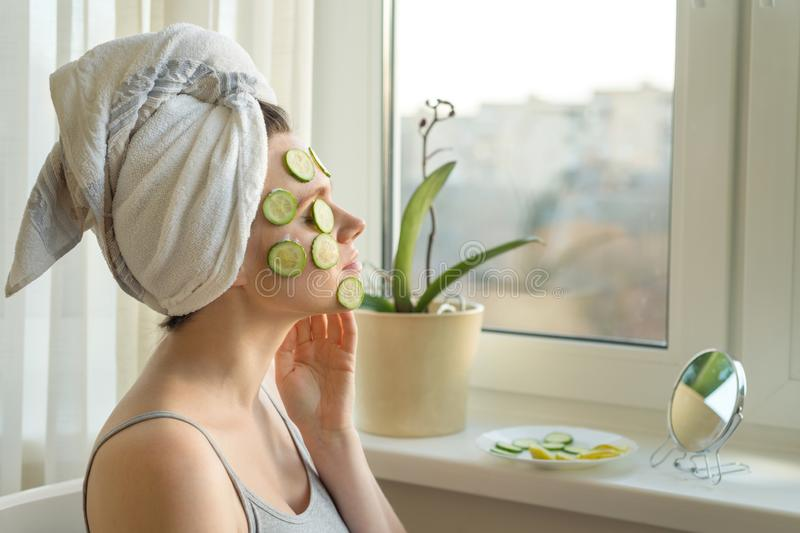 Young beautiful woman close-up at home near the window with natural homemade mask of cucumber on face, towel on head. Skin care,. Cosmetics, cosmetology stock images