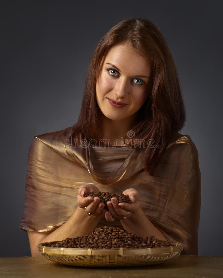 Young beautiful woman with coffee beans royalty free stock photography