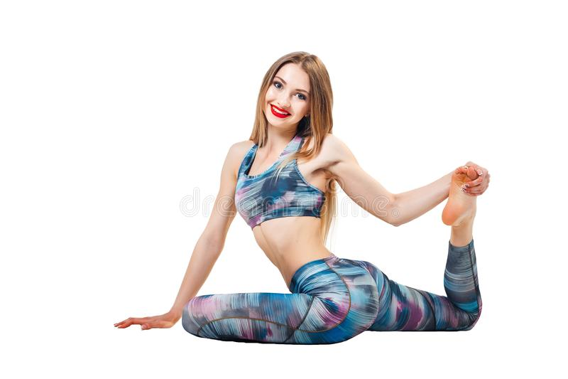 Young beautiful woman in color-blue top and leggings yoga posing isolated over white studio background and looking at camera. royalty free stock photos