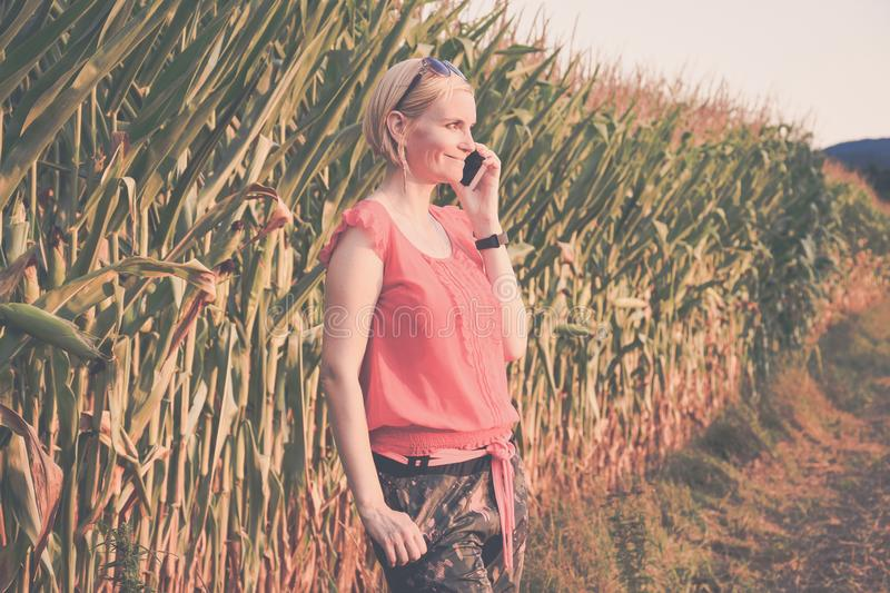 Young beautiful woman in colorful cloths and sunglasses outdoor talking on the cell phone royalty free stock photos