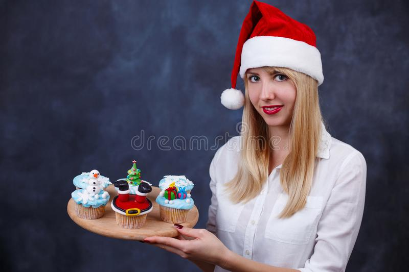 Young beautiful woman confectioner in Santa cap with decorated C stock photography
