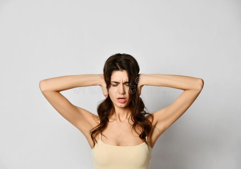 Young beautiful woman covers her ears with hands and frowns like she doesn`t want to hear something or has a terrible headache royalty free stock photo