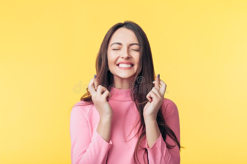 Young beautiful woman crossing her fingers and wishing for good luck over yellow background stock photos