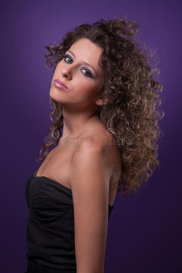 Young, beautiful woman with curly hair on purple royalty free stock photos