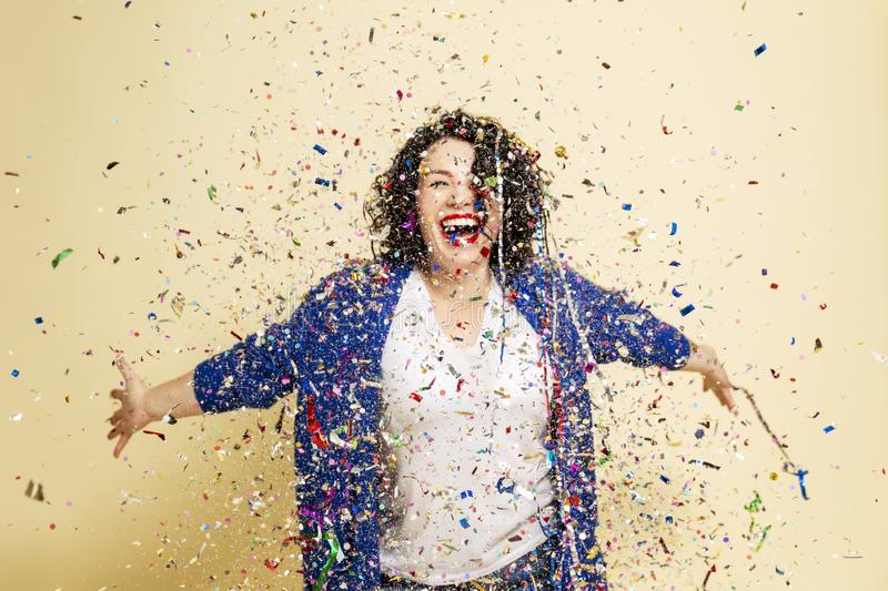 Young beautiful woman with curly hair sprinkled with confetti laughs. Festive mood. Isolated over white background royalty free stock photography