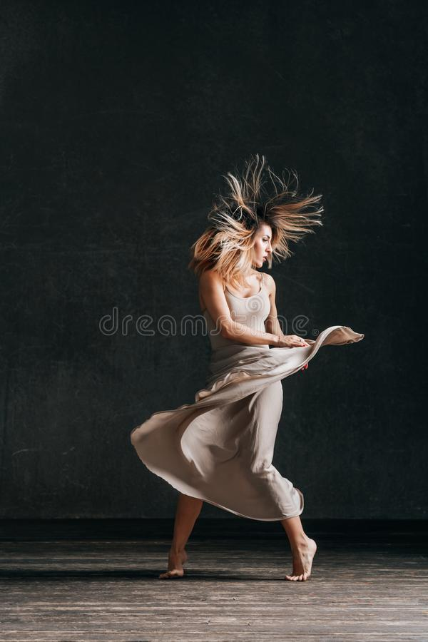 Young beautiful female dancer is posing in the studio. Young beautiful woman dancer posing in studio royalty free stock photo