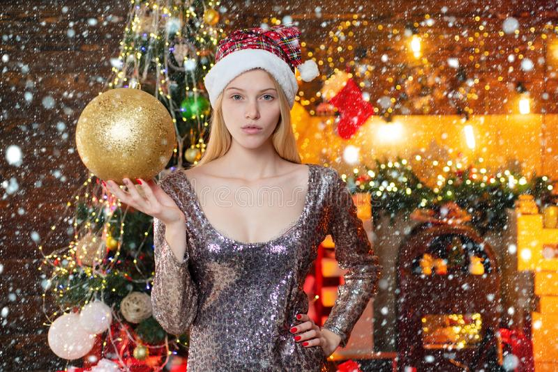Young beautiful woman decorating Christmas tree with bauble - New Year tradition. Woman in Christmas dress with bauble. Near the Christmas tree stock photos