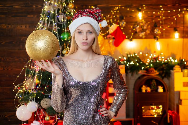 Young beautiful woman decorating Christmas tree with bauble - New Year tradition. Woman in Christmas dress with bauble. Near the Christmas tree royalty free stock photo