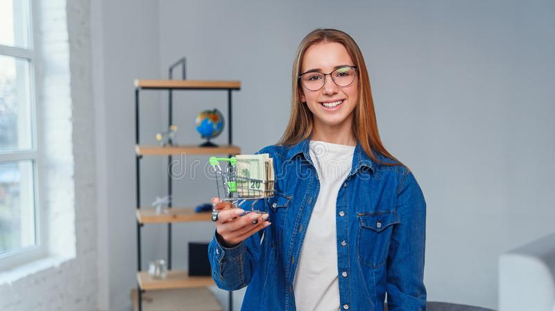 Young beautiful woman in denim shirt and eyeglasses holds small shopping cart full of US dollar. Shopping, saving money stock images