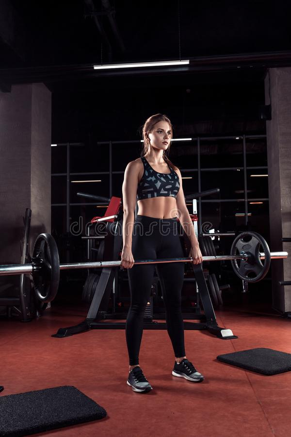 Young beautiful woman doing exercise with bar in a gym. Athletic girl doing workout in a fitness center. On a dark background the gym. Dressed in sport clothes stock photo