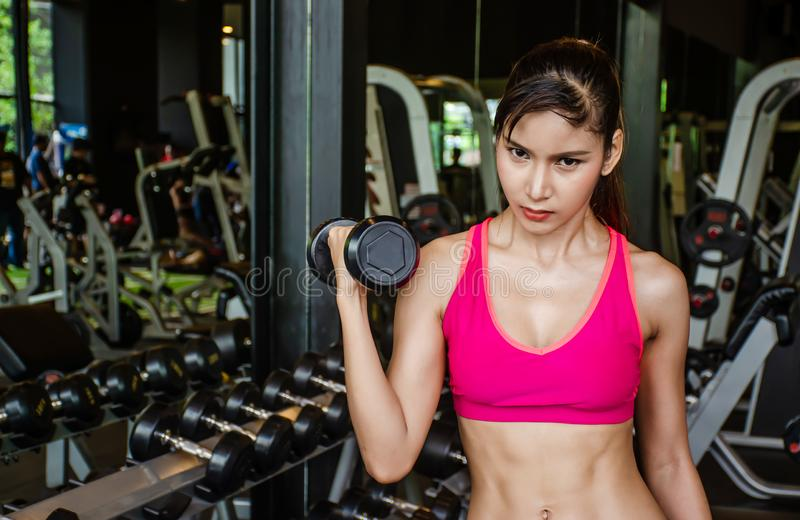Young beautiful woman doing exercises lifting dumbbell in gym.Glad smiling girl is enjoying with her training process royalty free stock images