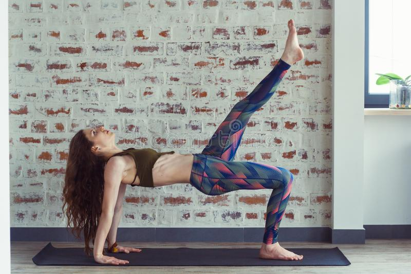 Beautiful woman in yoga class. Young beautiful woman doing exercises on yoga mat in front of a brick wall stock images