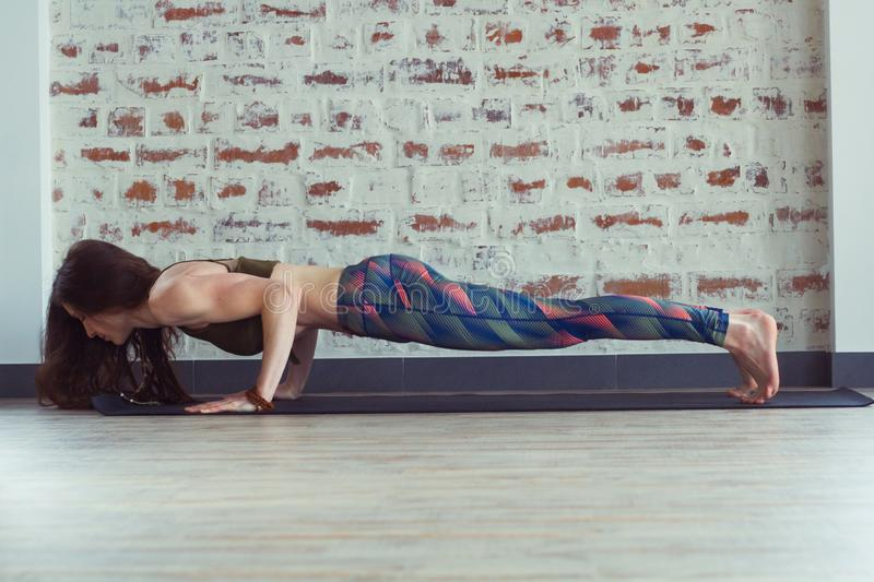 Beautiful woman in yoga class. Young beautiful woman doing exercises on yoga mat in front of a brick wall stock photo