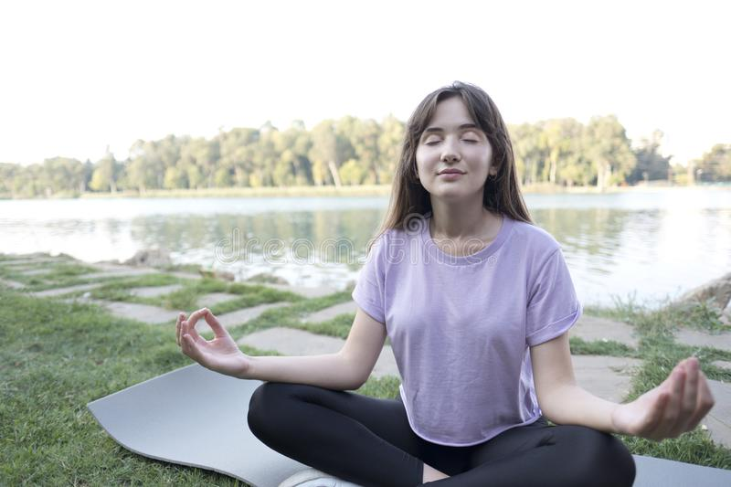 Young beautiful woman doing yoga exercises in park on the bank river. stock photos